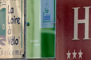 plaques d'information sur la façade de l'hotel la Tonnellerie affichant 3 étoiles et la label ecolabel européen