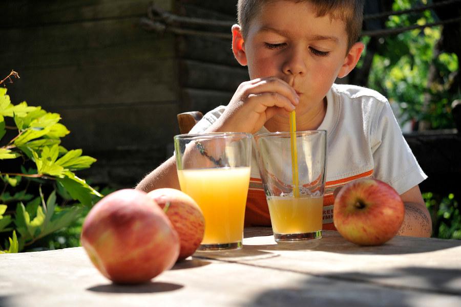 Enfant boit un verre de jus de fruits sur une terasse au soleil